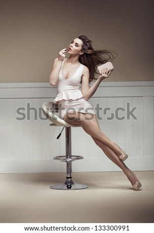 Sexy woman sitting on a chair - stock photo