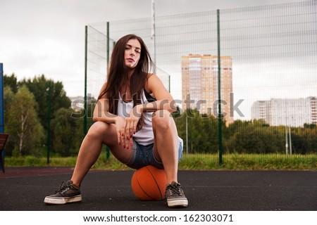 Sexy Woman Sitting On Basketball On Sports Playground - stock photo