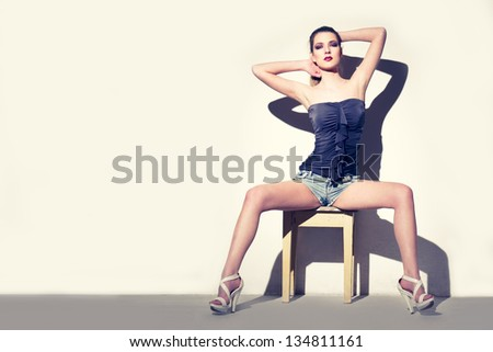Sexy woman sitting on stool at wall - stock photo