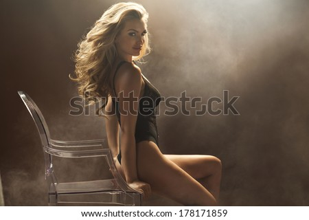 Sexy woman sitting on the crystal chair - stock photo