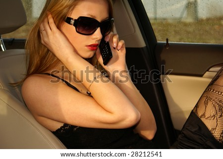 Sexy woman talking on the phone in the luxury car
