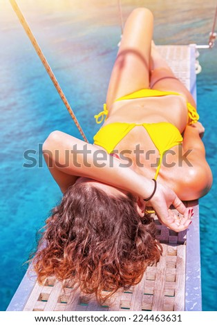 Sexy woman tanning on sailboat, female relaxing above transparent blue sea, girl enjoying bright sun light, active lifestyle, happy summer vacation - stock photo
