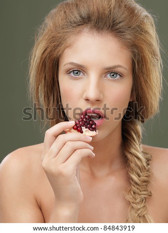 sexy woman tasting a piece of pomegranate - stock photo