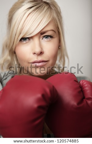 sexy woman wearing boxing gloves looking at camera - stock photo