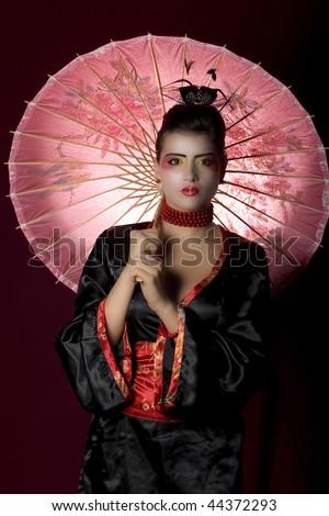 Sexy woman wearing geisha costume, holding an umbrella and looking at the camera. Studio shot - stock photo