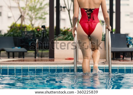 Sexy woman wearing red swimsuit in swimming pool. - stock photo
