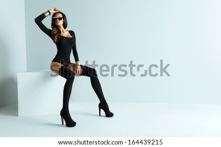 Sexy woman wearing sunglasses and black stockings - stock photo