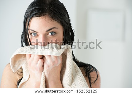 Sexy woman wiping herself with towel after taking shower at home and looking at camera - stock photo