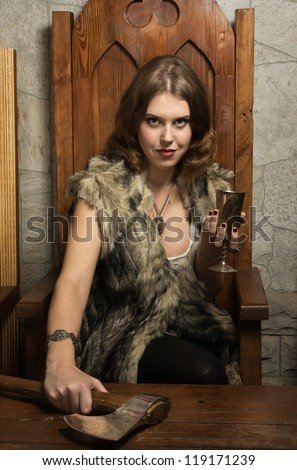 Sexy woman with a cup of wine in a medieval castle interior