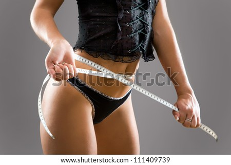 Sexy woman with a perfect figure measures the waist - stock photo