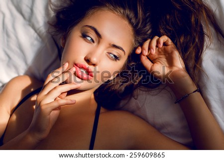 Sexy woman with amazing blue eyes and full lips lying   on pillow in her bedroom. - stock photo