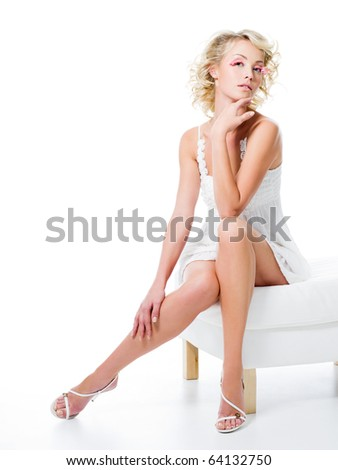 sexy woman with beautiful legs sits on white chair - stock photo