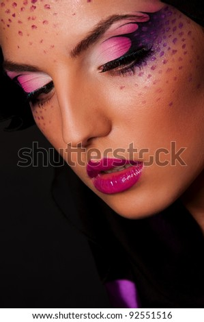 sexy woman with creative face art on black background - stock photo