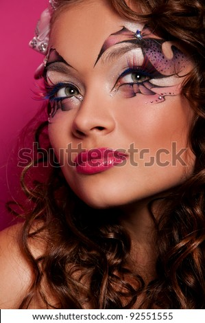 sexy woman with creative face art on pink background