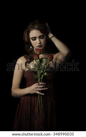 Sexy woman with dark makeup and a red dress, posing with roses in her hand while holding her auburn red hair back. - stock photo