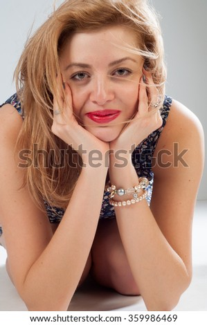 Sexy woman with glasses in a flower dress. High caucasian attractive cheerful happy sexy female model brunette hair shakes her head in the studio - stock photo