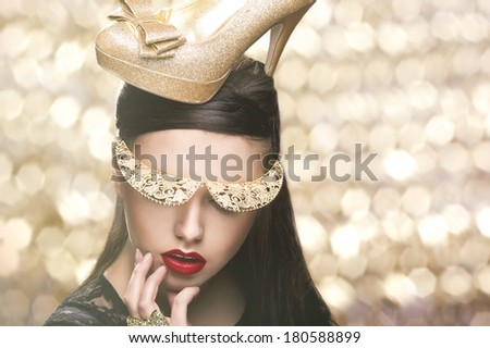 Sexy woman with gold shoe on head - stock photo