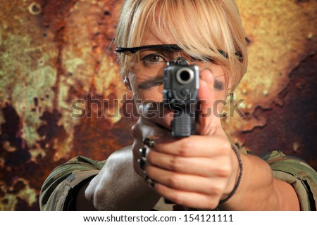 Sexy woman with gun over grunge background - stock photo