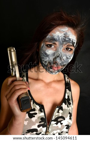 sexy woman with gun with camouflage painting - stock photo