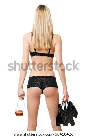 Sexy woman with handbag and bottle in her hands. Rear view - stock photo
