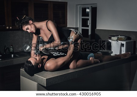 Sexy woman with knife lying from above her boyfriend which smoking a cigarillo