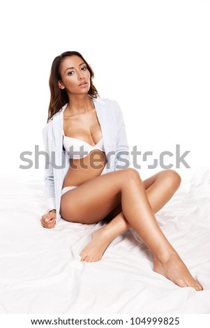 Sexy woman with large breasts in white lingerie and a shirt sitting relaxing on a bed - stock photo