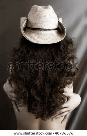 Sexy woman with long brown curly hair in cowboy hat