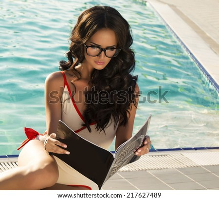 sexy woman with long dark hair in swimsuit and glasses reading magazine beside a swimming pool - stock photo