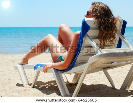 sexy woman with long legs is lying on a beach chair