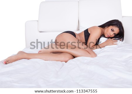 Sexy woman with long shapely bare legs posing in bed in black lingerie - stock photo