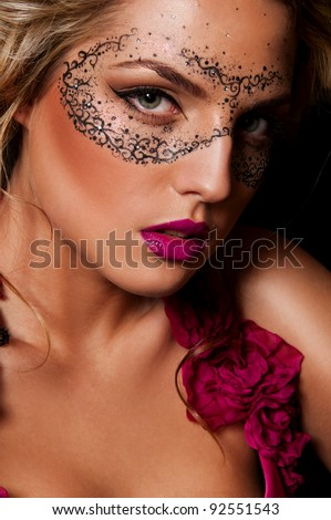 sexy woman with mask on face with creative face art - stock photo