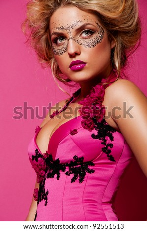 sexy woman with mask on face with creative face art on pink background - stock photo