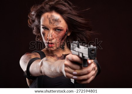Sexy woman with military, riot uniform in studio on dark red background. With gun and blood drop on face.