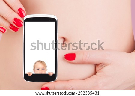 Sexy woman with red nails holding mobile phone with pregnancy test against her belly. The future of medicine, high tech. - stock photo
