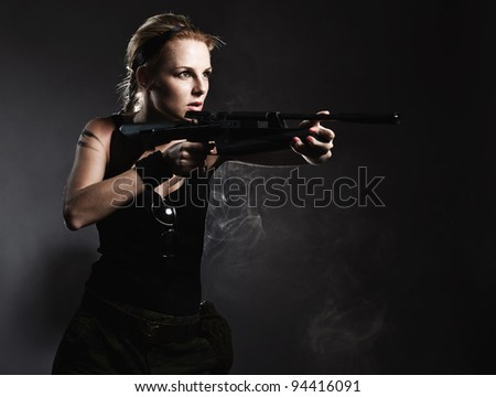 Sexy woman with rifle on dark - stock photo
