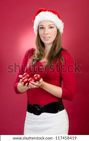 Sexy woman with santa hat holding christmas balls - stock photo