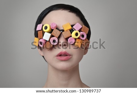 sexy woman with sort hair wear glasses made up from sweets