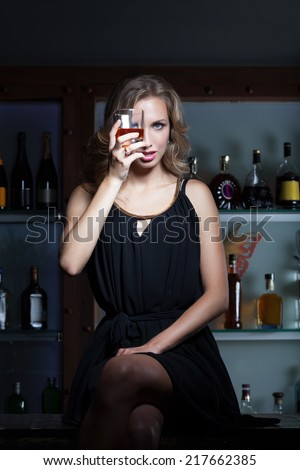 Sexy woman with the glass of whiskey sitting on the bar counter - stock photo