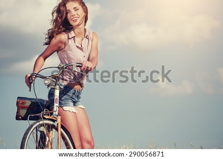 Sexy woman with vinntage bike in a country road. - stock photo