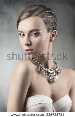 sexy woman with white bra posing in close-up beauty portrait with creative shiny make-up, plait hairdo and fashion big necklace. Looking in camera with charming expression  - stock photo