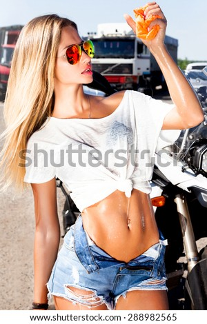 Sexy woman worker washing car's alloy wheels on a car and motorcycle wash.Sexy wit body,wet chic,sexy abs press.denim shorts.wet T-shirt,aviator sunglasses,gold tan skin,wet body,wash motorcycle - stock photo