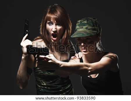 Sexy women holding gun on gray - stock photo
