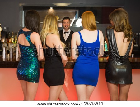 Sexy women ordering drinks standing back to camera in a nightclub - stock photo