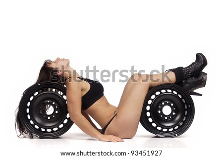 Sexy worker posing against a white background with black wheels - stock photo