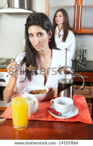 Sexy young adult brunette roommates in lingerie eating breakfast and drinking coffee in their kitchen before work