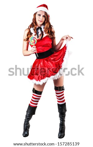 sexy young adult woman wearing santa claus clothes and holding lollipop