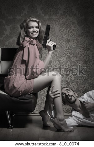 Sexy young adult woman with handgun sitting over man lying on floor and begging for mercy. - stock photo