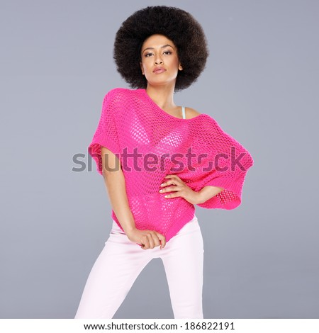 Sexy young African American woman with a frizzy afro hairstyle wearing a stylish pink blouse posing with her hand on her hip, square format on grey - stock photo