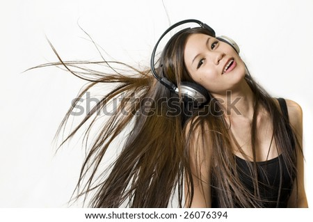 Sexy young Asian girl listening to music on headphones - stock photo