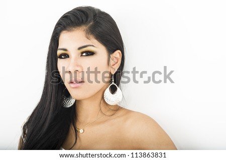 Sexy young Asian woman wearing large dangling earrings looking at the camera with a sultry look, studio portrait with copyspace